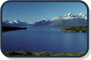 Photograph of crystal blue BC coast fiord with snow capped mountains in background.
